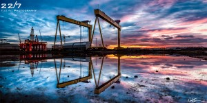 Panoramic Landscape photograph of sunrise at Harland and Wolff shipbuilders, Belfast, Northern Ireland by award winning landscape and fine art photographer '22/7 fine art photography' from Ballyroney, Banbridge, County Down, Northern Ireland. Red and Blue vibrant sky with Samson & Goliath gantry cranes reflected and mirrored via the puddle on the ground.